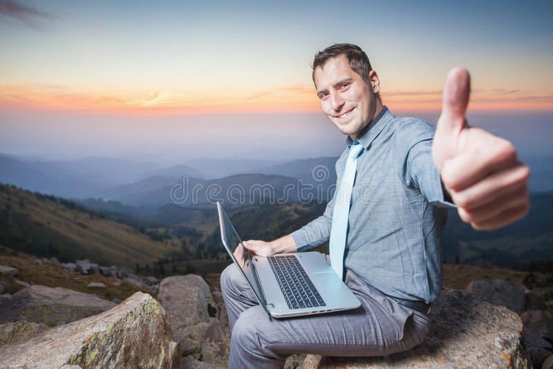 Lyckad affärsman överst av berget, genom att använda en bärbar dator royaltyfri bild