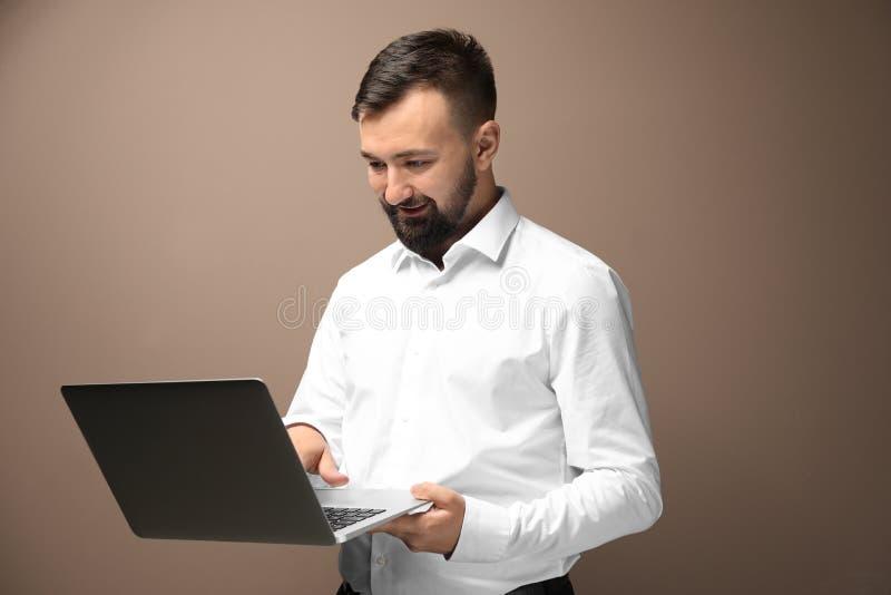 Lyckad affärsman med bärbara datorn på färgbakgrund royaltyfri foto