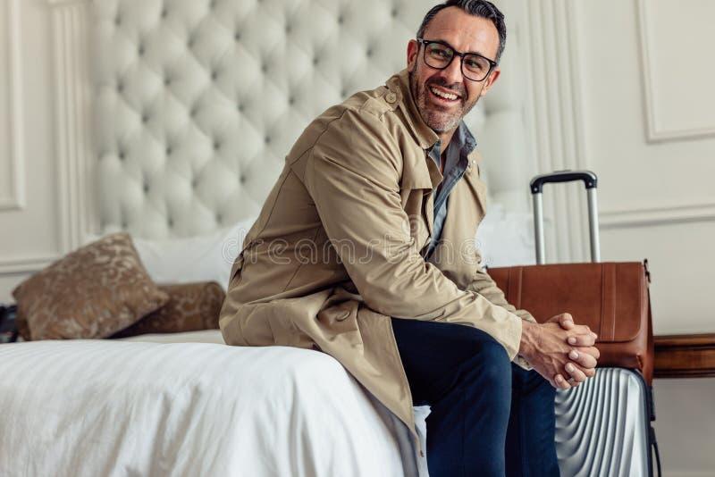 Lyckad affärsman med bagage som sitter i hotellrumsäng och bort ser Mogen affärsman på affärstur royaltyfri foto