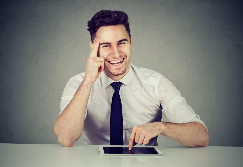 Lyckad affärsman med minnestavlasammanträde på skrivbordet som ler se kameran royaltyfri foto