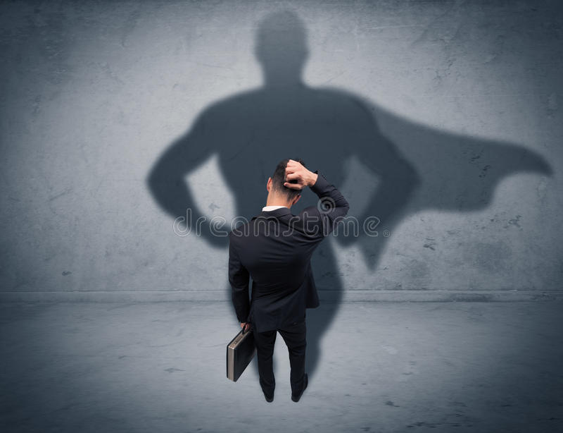 Lyckad affärsman med superheroskugga royaltyfri foto