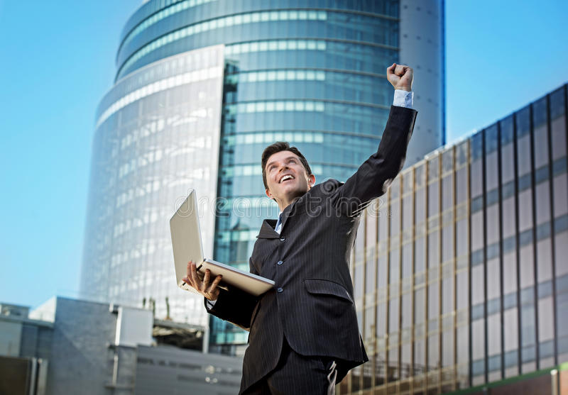 Lyckad affärsman med tecknet för seger för datorbärbar dator det lyckliga görande royaltyfria foton