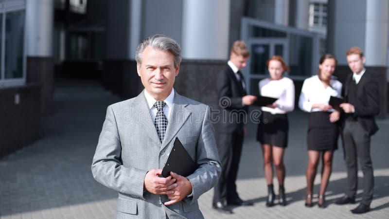 Lyckad affärsman på bakgrund av kontorsbyggnad royaltyfri foto