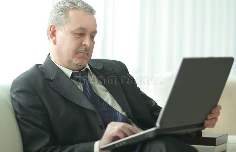 Lyckad affärsman som använder bärbara datorn som i regeringsställning sitter lobbyen royaltyfri foto