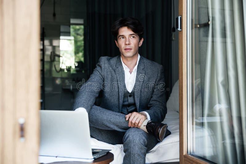 Lyckad affärsman som arbetar med bärbara datorn, medan sitta på en säng på hotellrummet royaltyfri bild