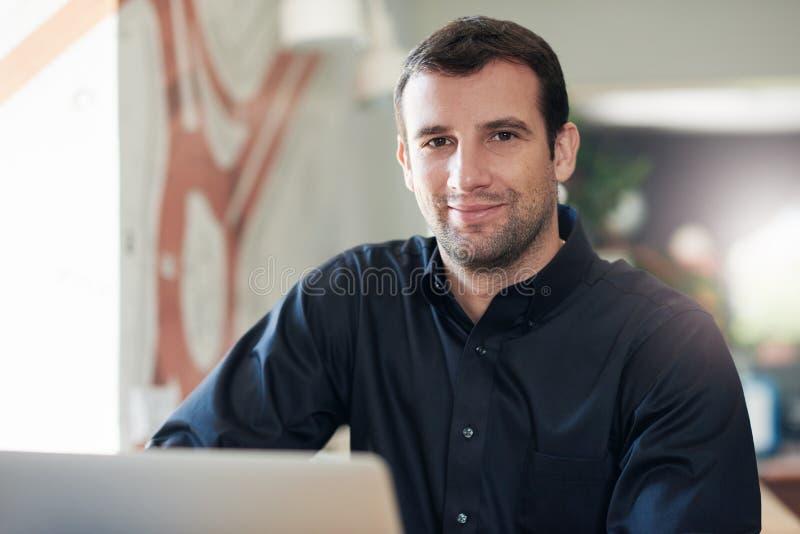 Lyckad affärsman som ler och använder en bärbar dator i ett kontor arkivbild