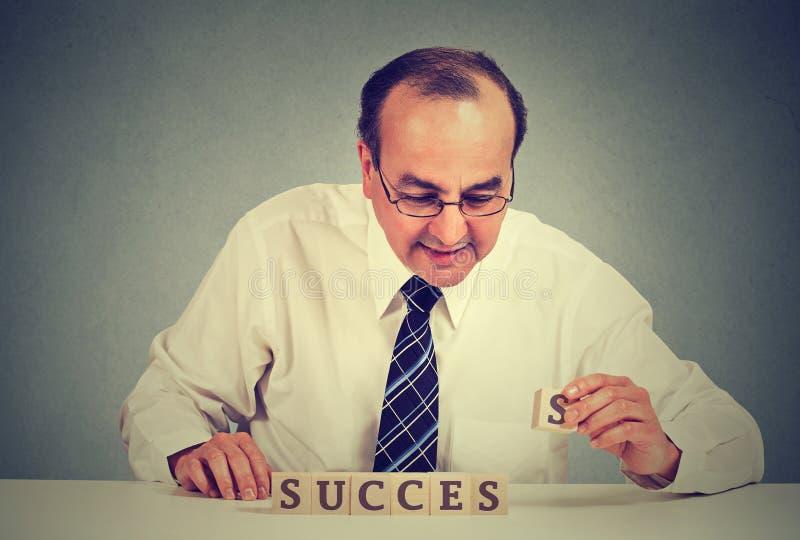 Lyckad affärsman som ordnar träkuber som läser framgång royaltyfri foto