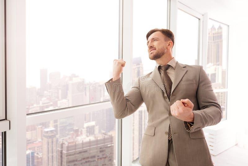 Lyckad affärsman som står det near kontorsfönstret royaltyfri foto
