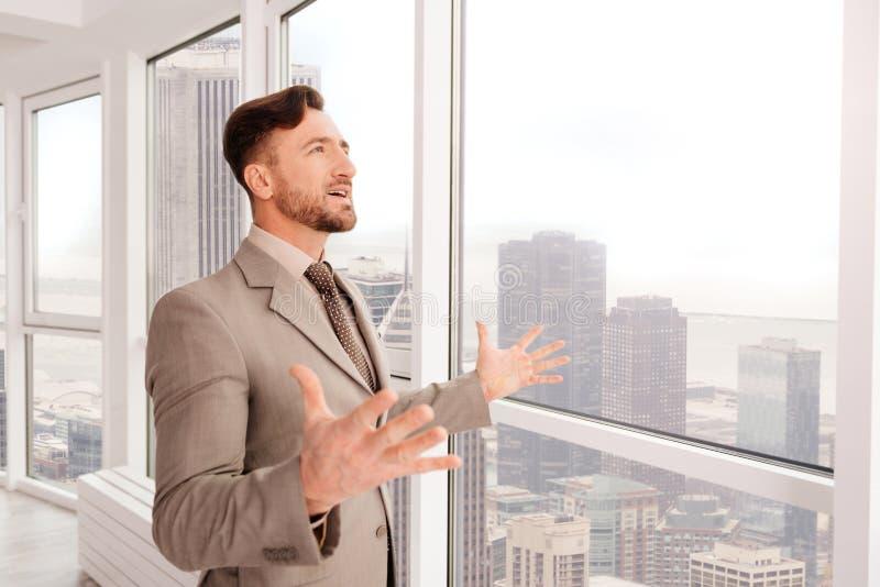 Lyckad affärsman som tycker om sikten från hans kontor arkivbild