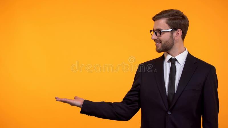 Lyckad aff?rsman som str?cker handen p? orange bakgrund, st?lle f?r mall royaltyfri fotografi