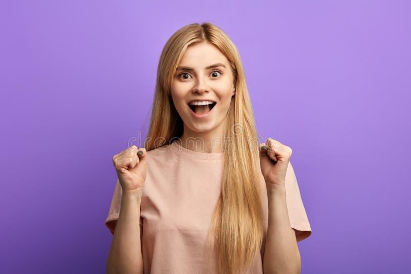 Lyckad blond flicka med lyftta händer som ropar och firar framgång arkivfoton