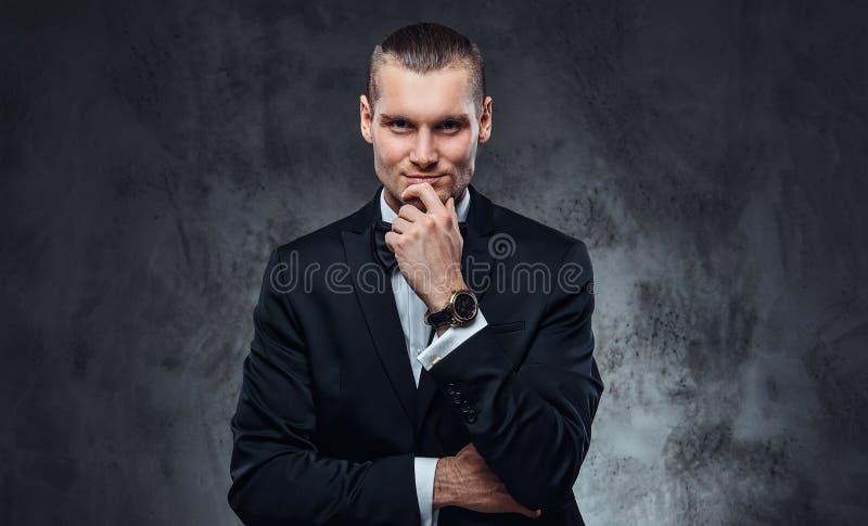 Lyckad elegantly klädd man som bär en svart klassisk dräkt och fluga som ser en kamera royaltyfria bilder