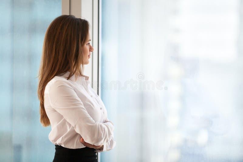 Lyckad fundersam kvinnaföretagsledare som ser ut ur stor w royaltyfri foto