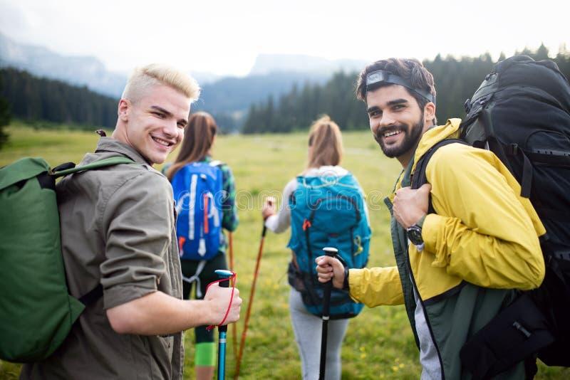Lyckad grupp av lyckliga v?nner p? berg?verkant som hurrar arkivfoto