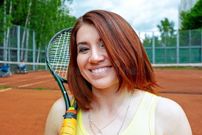 Lyckad idrottskvinna med racket på tennisbanan Sund livsstil royaltyfria foton