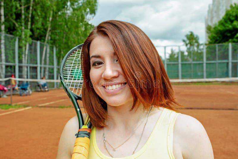 Lyckad idrottskvinna med racket på tennisbanan Sund livsstil royaltyfri fotografi