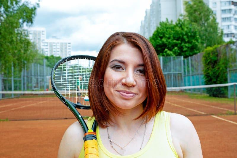 Lyckad idrottskvinna med racket på tennisbanan Sund livsstil arkivbilder