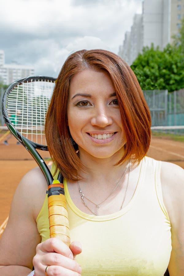 Lyckad idrottskvinna med racket på tennisbanan Sund livsstil arkivfoton