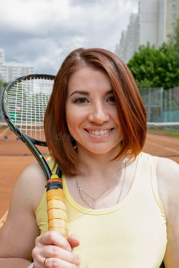 Lyckad idrottskvinna med racket på tennisbanan Sund livsstil royaltyfri foto
