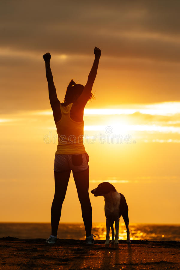 Lyckad konditionkvinna och hund arkivbilder
