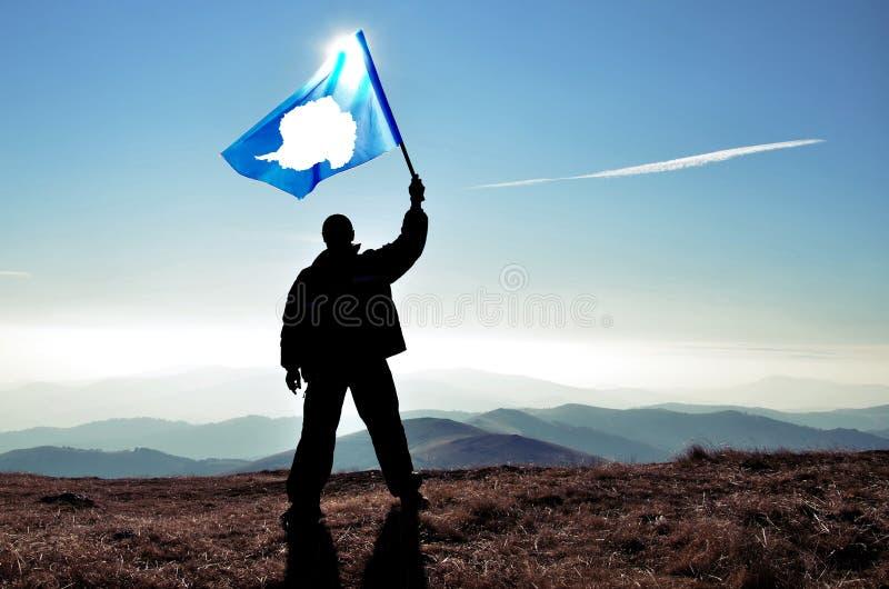Lyckad konturmanvinnare som vinkar den Antarktis flaggan fotografering för bildbyråer