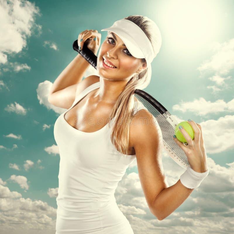 Lyckad kvinna med racket på tennisbanan royaltyfri bild