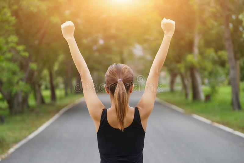Lyckad kvinna som lyfter armar efter arg spårspring på sommarsolnedgång Kvinnlig idrottsman nen för kondition med armar som firar royaltyfri bild
