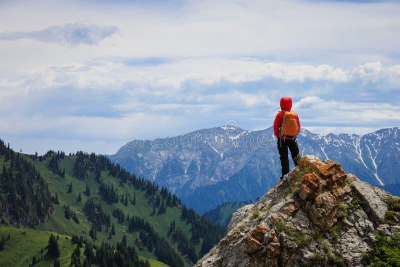 Lyckad kvinnafotvandrare som fotvandrar på klippan för bergmaximum royaltyfri foto