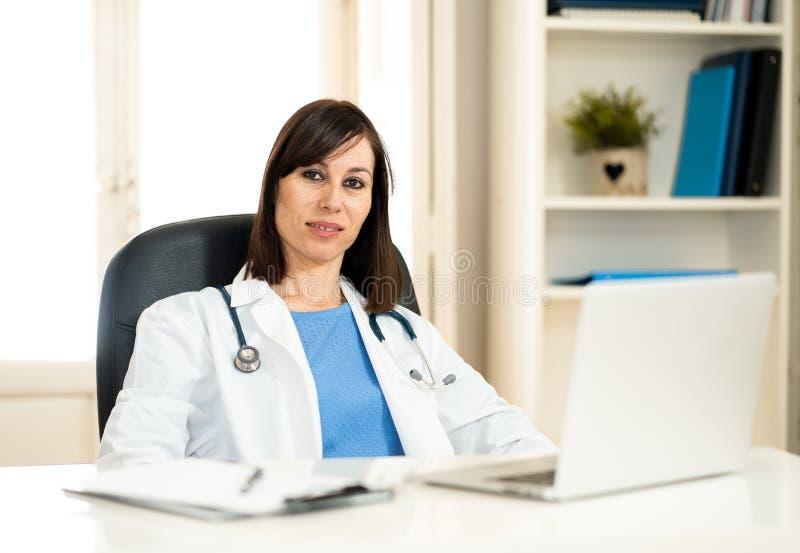 Lyckad kvinnlig doktor som arbetar i kliniksjukhuskontoret som ler och poserar för kameran royaltyfri fotografi