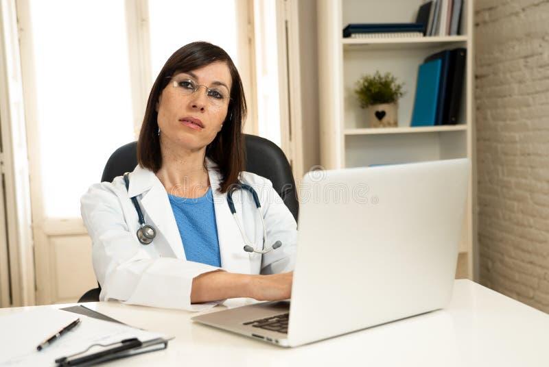 Lyckad kvinnlig doktor som arbetar i kliniksjukhuskontoret som ler och poserar för kameran royaltyfri foto