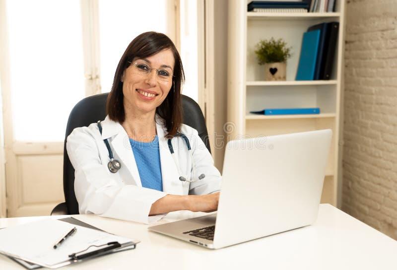 Lyckad kvinnlig doktor som arbetar i kliniksjukhuskontoret som ler och poserar för kameran royaltyfria bilder
