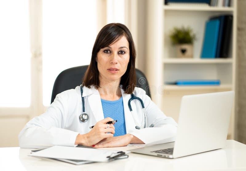 Lyckad kvinnlig doktor som arbetar i kliniksjukhuskontoret som ler och poserar för kameran fotografering för bildbyråer