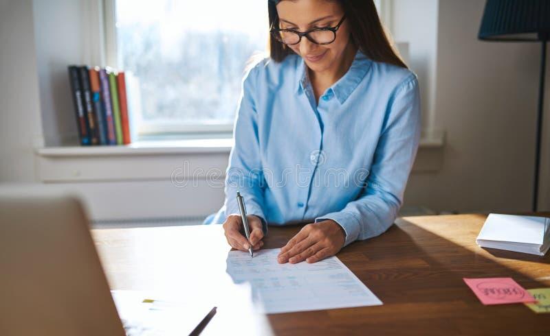 Lyckad kvinnlig entreprenör som arbetar på hennes skrivbord arkivbild