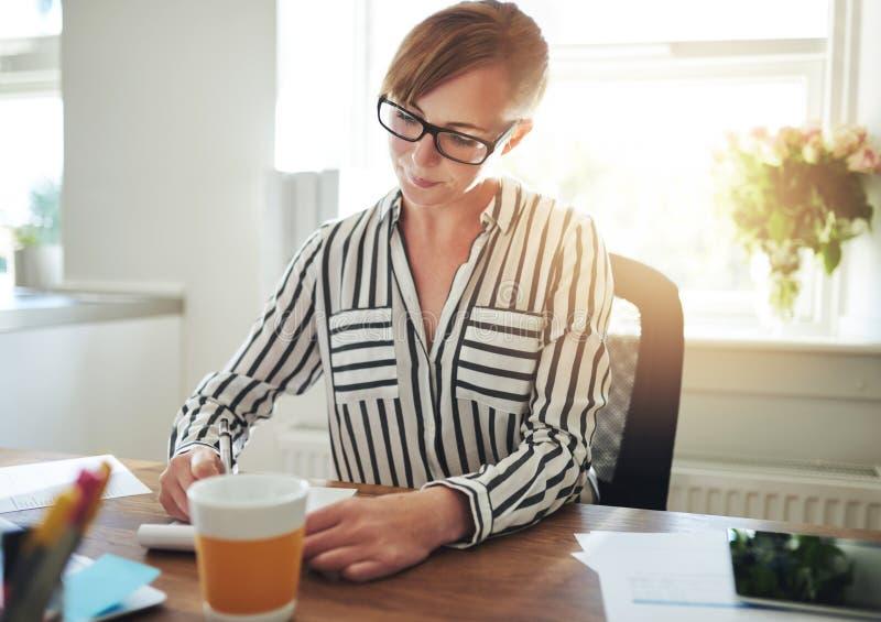 Lyckad kvinnlig entreprenör som hemma arbetar arkivfoto