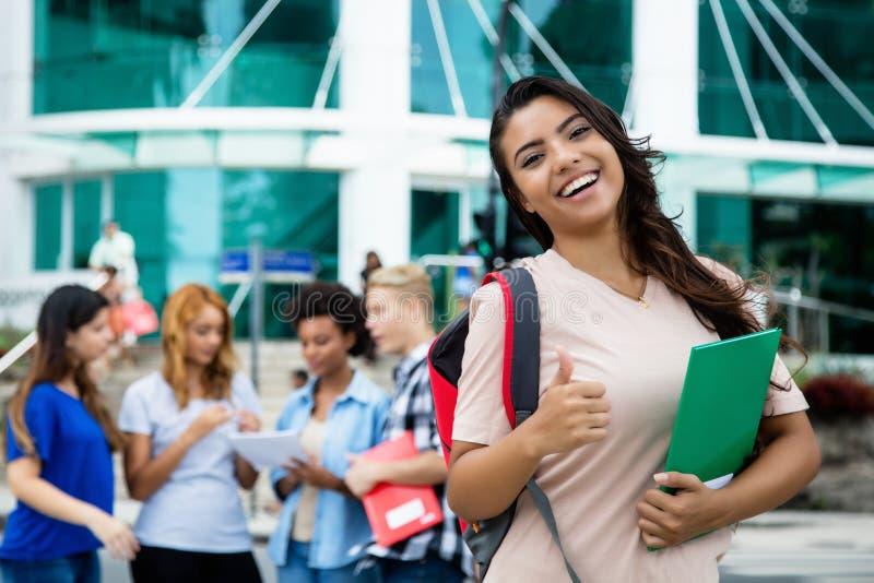 Lyckad latin - den amerikanska visningen för kvinnlig student tummar upp royaltyfri foto