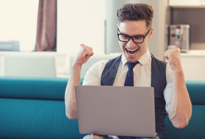 Lyckad man med bärbara datorn som är upphetsad med seger royaltyfri foto