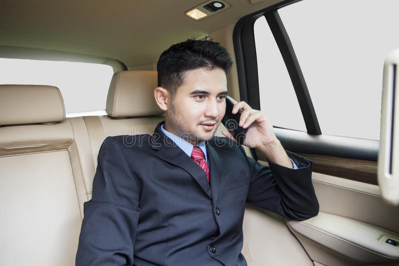 Lyckad man som talar på telefonen i bil fotografering för bildbyråer