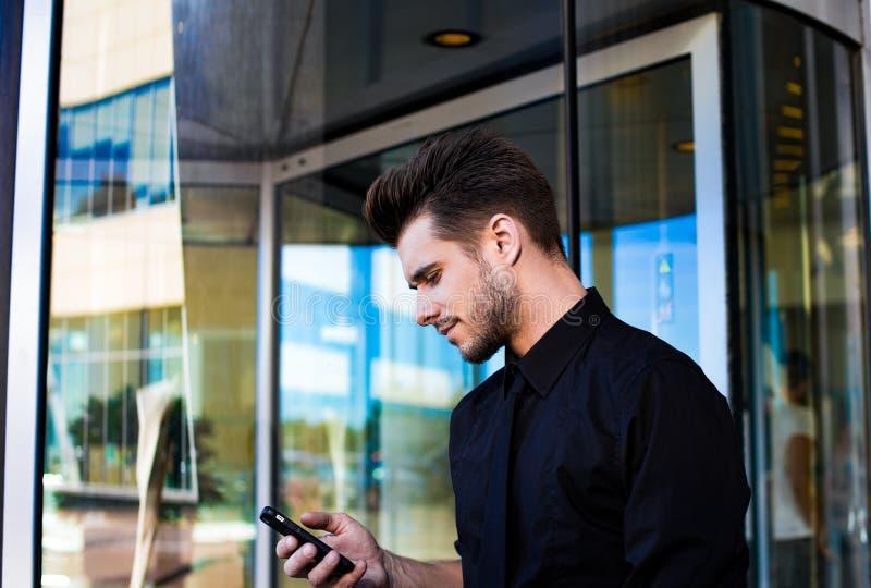 Lyckad manlig finansiär som kontrollerar mejl i internet via mobiltelefonen som står utanför företaget royaltyfria foton