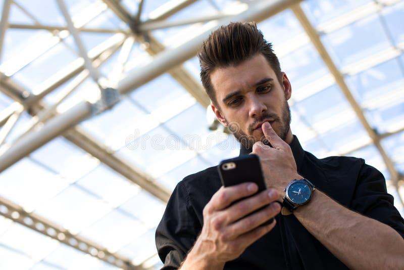 Lyckad manlig kompetent chef som använder applikationer på mobiltelefonen under arbetsdag royaltyfri fotografi
