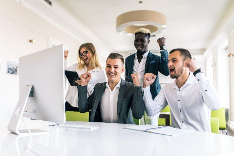 Lyckad multietnisk affärsgrupp som firar på kontoret arkivbilder