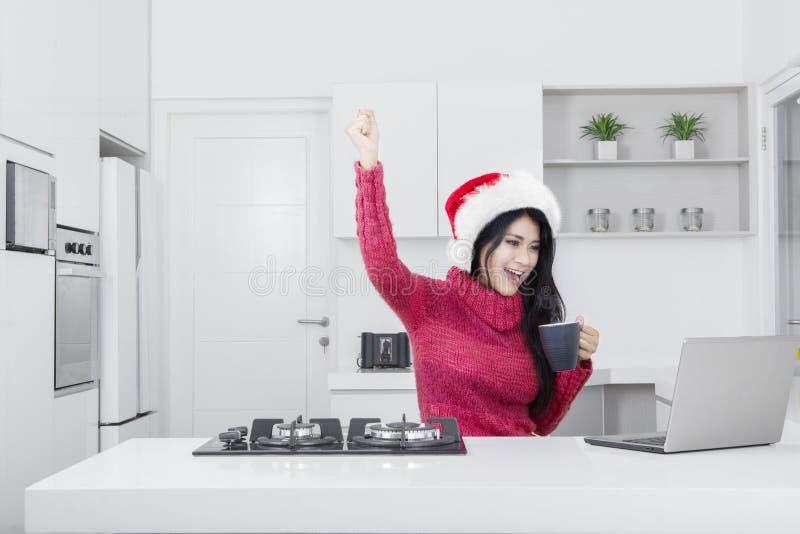 Lyckad nätt flicka med bärbara datorn och jultomtenhatten royaltyfri foto