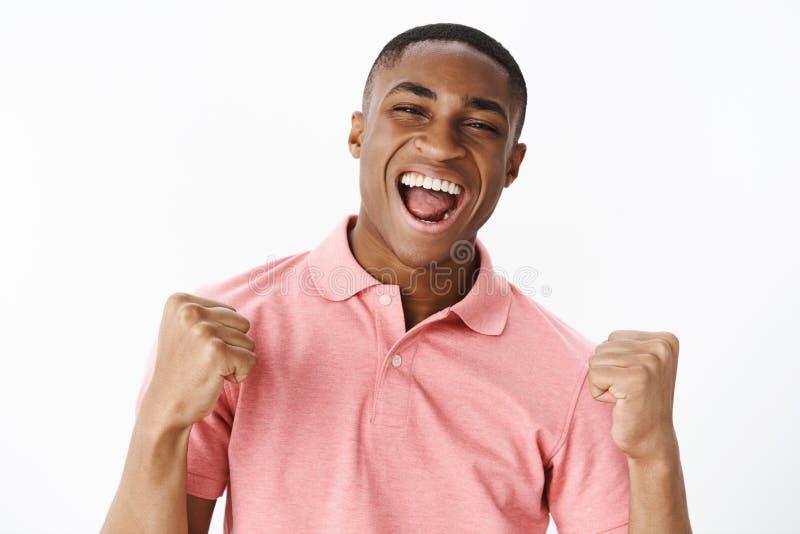 Lyckad nöjd och lycklig stilig ung afrikansk amerikangrabb i rosa skjorta som griper hårt om nävar i seger och jubel fotografering för bildbyråer
