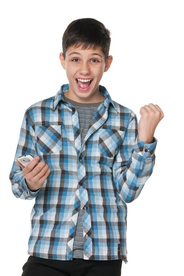 Lyckad pojke med en mobiltelefon royaltyfri bild