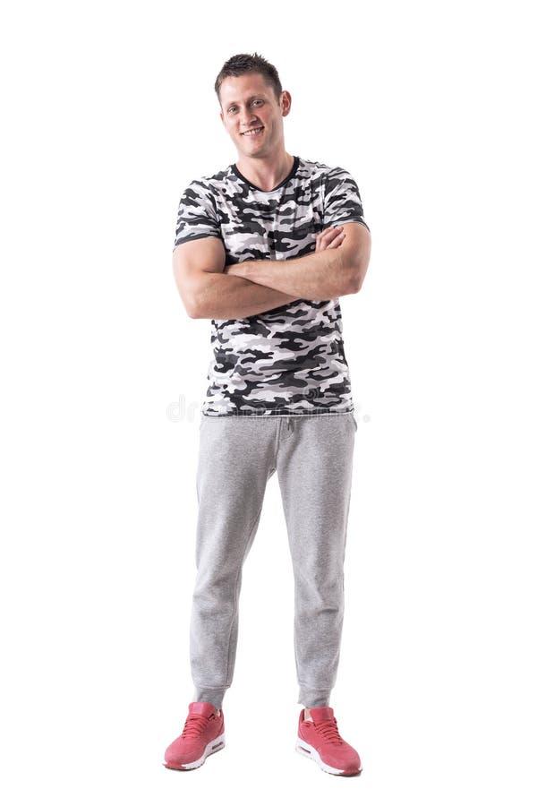 Lyckad säker lycklig ung sportig man i arméskjorta med korsade armar som ler på kameran arkivbild