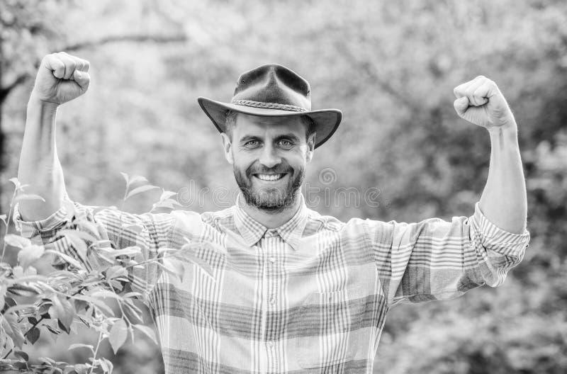 Lyckad sexig bonde muskul?s ranchman i v?xter f?r omsorg f?r cowboyhatt Lantbruk och jordbruk Arbeta i tr?dg?rden ranchen Eco lan arkivbilder