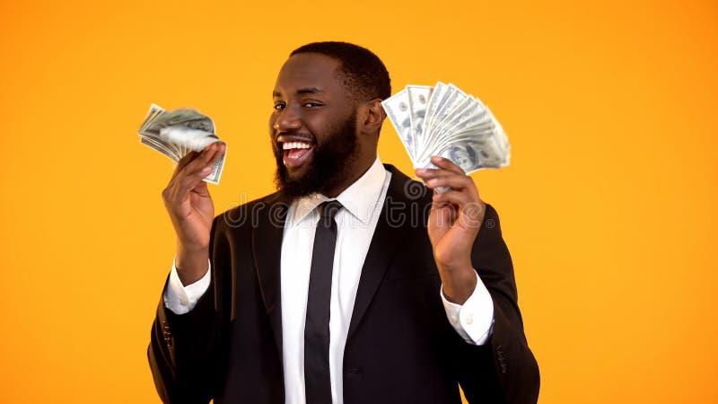 Lyckad svart man i aff?rsdr?kten som rymmer grupper av kassa och att le f?r dollar royaltyfria foton