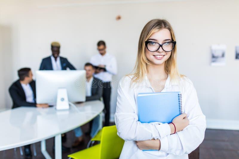 Lyckad ung affärskvinna i exponeringsglas som framme står av den mång- folkgruppen av folk i regeringsställning fotografering för bildbyråer