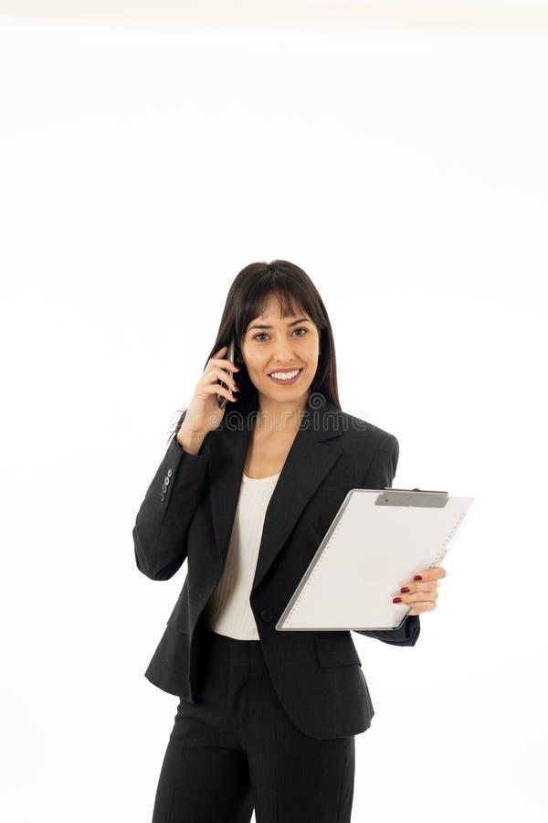 Lyckad ung affärskvinna som talar på telefonen som rymmer en mapp bakgrund isolerad white arkivfoton