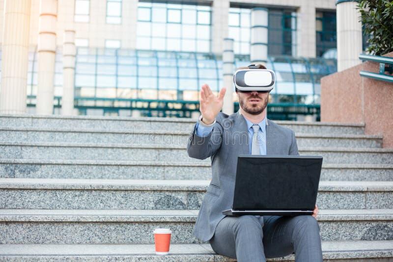 Lyckad ung affärsman som använder VR-skyddsglasögon och gör handgester som framme arbetar på en bärbar dator av en kontorsbyggnad arkivbild