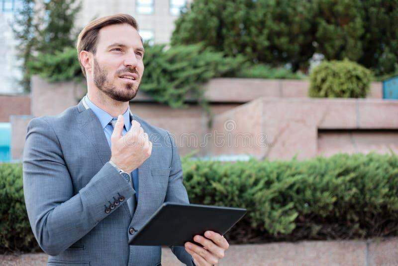 Lyckad ung affärsman som framme arbetar på en minnestavla av en kontorsbyggnad Rymma handen på hakan och se in i avstånd royaltyfria bilder